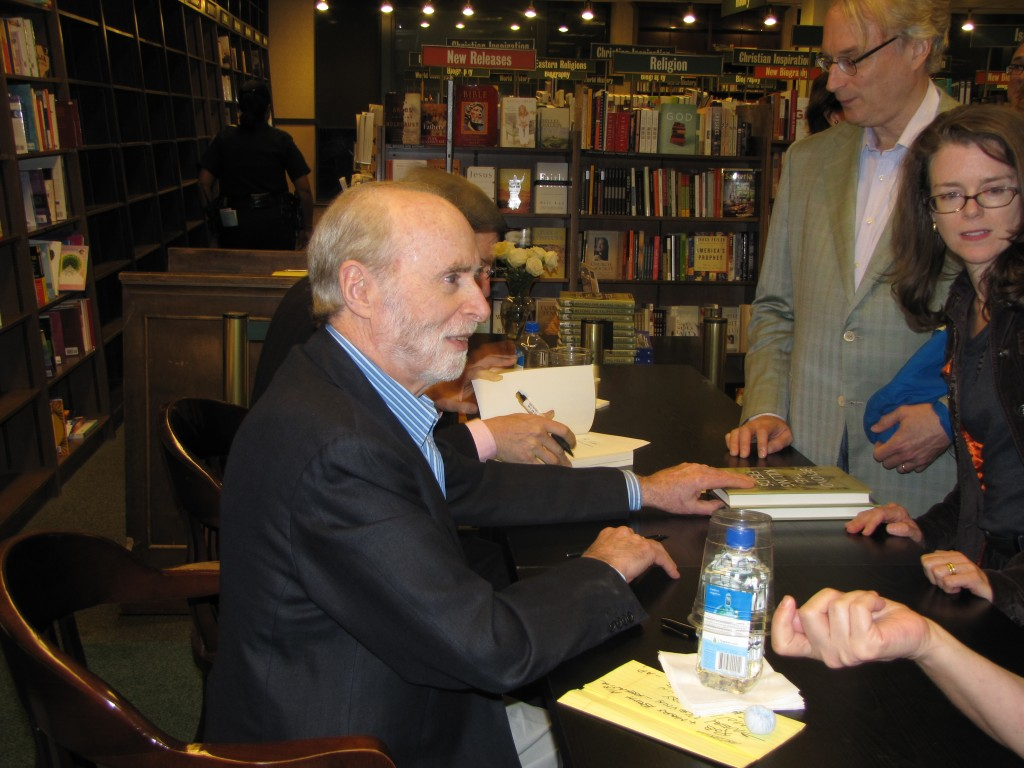 Sydney Schanberg autographs copies of his book Beyond the Killing Fields